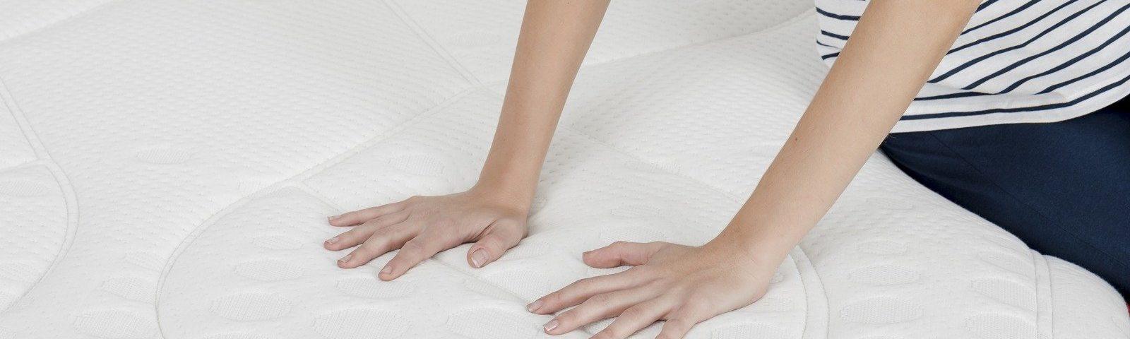 Mujer tocando la firmeza del colchón