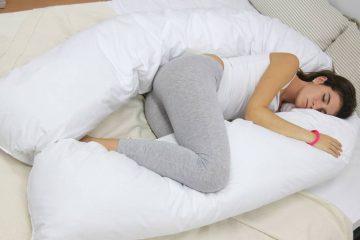 mujer dormida de lado con una almohada grande